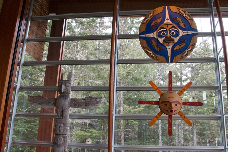 The Squamish Lilwat Cultural Centre - Carved objects and totem pole with glass and forest behind.